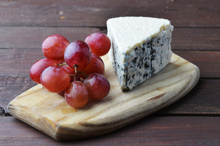 tabla de quesos: pieces of blue cheese and red grapes on a wooden table