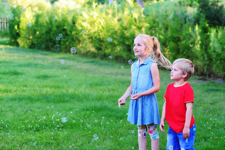 blower: girl and boy play with bubble blower on green lawn. Stock Photo