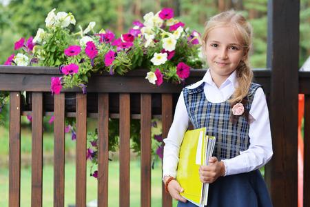 colegiala: La pequeña colegiala bonita con los libros cerca de valla con flores Foto de archivo