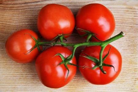 tomate: tomates rouges avec la branche sur fond de bois Banque d'images