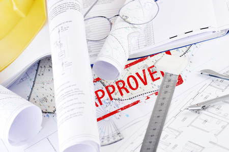 yellow helmet: Yellow helmet and heap of project drawings Stock Photo