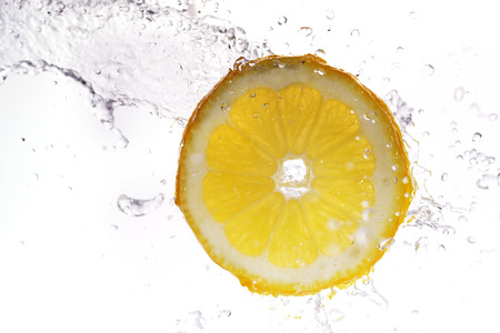 lemon water: slice of lemon in  water with bubbles