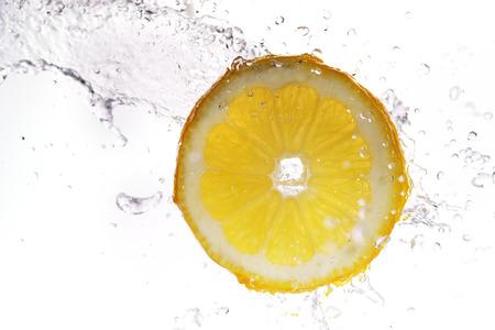 lemon water: slice of lemon in  water with bubbles