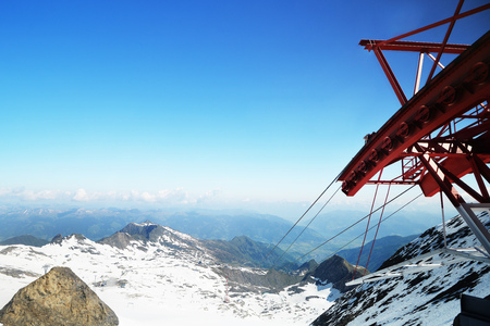 cloud capped: Cable car railway on capped mountain peaks and blue sky