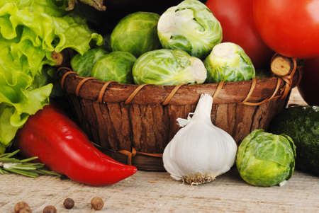 wooden basket: Composition with vegetables in wicker basket on wooden board Stock Photo