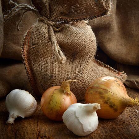 sacco juta: Aprire sacco di iuta con cipolle mature e aglio sulla tavola di legno Archivio Fotografico