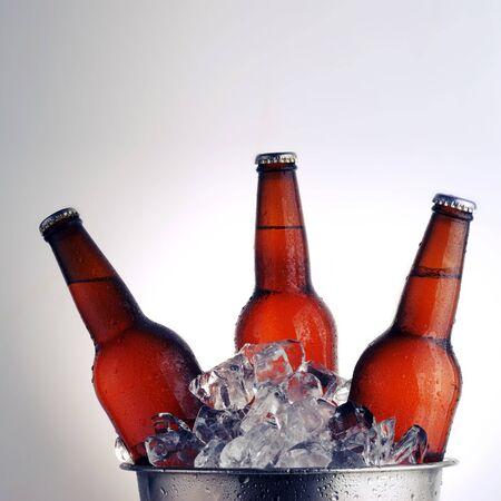 condensation: Three brown beer bottles in ice bucket with condensation