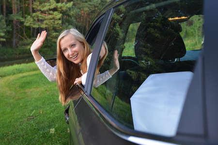 sit: Smiling woman sit in car.