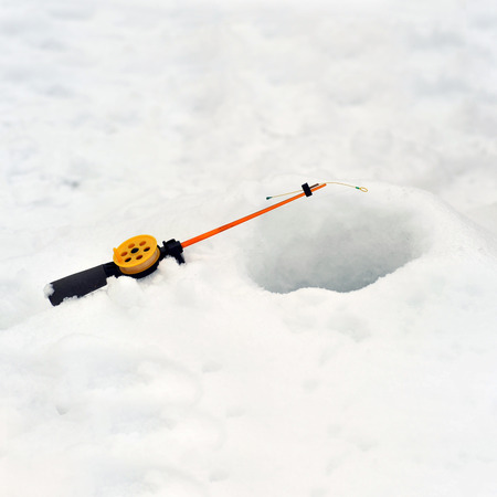 drilled: Fishing line in  hole drilled in ice Stock Photo