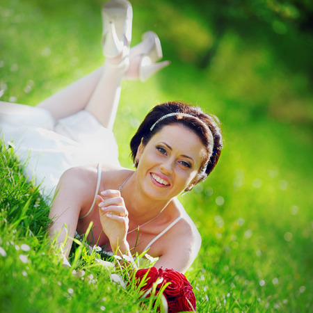 bride in white dress lying down in  grass. photo