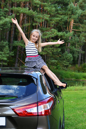 little girl sit on car roof Stock Photo