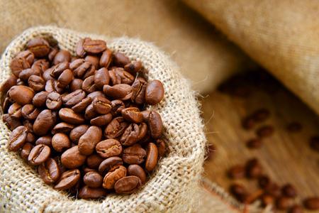 sacco juta: chicchi di caffè torrefatto nel sacco di iuta su fondo in legno
