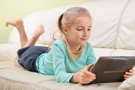 electronic music: girl with modern tablet lying on sofa