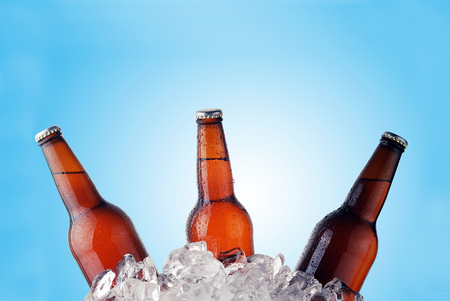 brown bottles: brown bottles of beer chilling on ice Stock Photo
