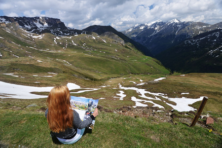 slope: young woman sitting on  mountain slope Stock Photo