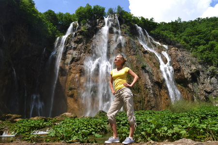 young woman near beautiful waterfalls on slopes of mountains