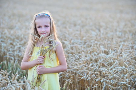 beautiful girl holding sheaf  of wheat