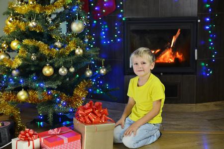 ittle: ittle boy looks gifts near Christmas tree