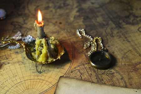 candle lie on old ancient map Stock Photo