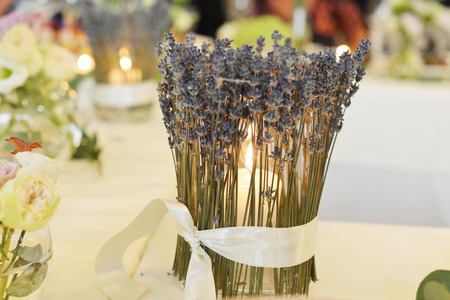 candle-holder, decorated with lavender, burns on table