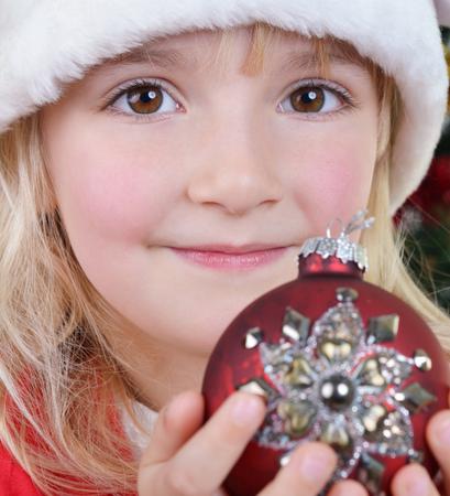 adorable little girl holding christmas ball near Christmas fir-tree Stock Photo
