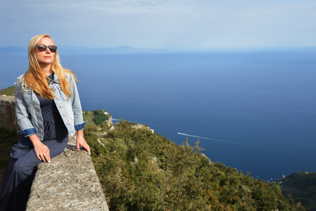 Woman sits on stone fence of mountain road Stock Photo