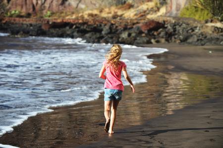 cute girl is playing on sandy beach Stock Photo