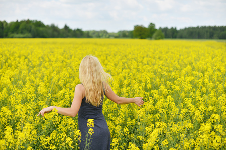 Charming woman at  field of canola Stock Photo
