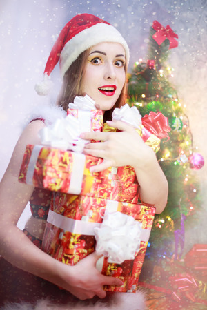 ttractive: Sexy blonde girl with gift box smiling and wearing Santa Claus clothes.