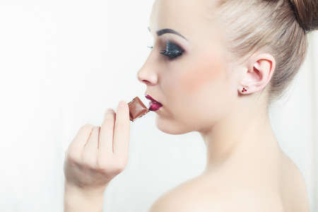 portret: Fashion portret of attractive young woman eat a chocolate Stock Photo
