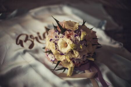The bride's bouquet sits on the pajamas on which the bride writes Foto de archivo