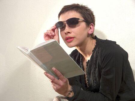 sunglassess: Woman with sunglassess is reading book Stock Photo