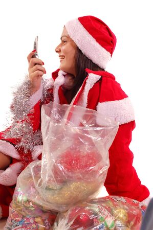 A young Santa Claus with gifts talking on mobil phone looking foward and waiting  Christmass and New Years holideys photo