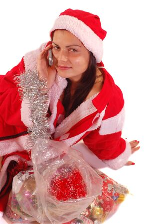 A young Santa Claus is talking on mobil phone looking foward and waiting  Christmass and New Years holideys photo