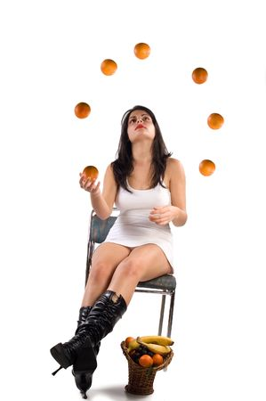 Young brunette woman sitting and juggling with orange photo