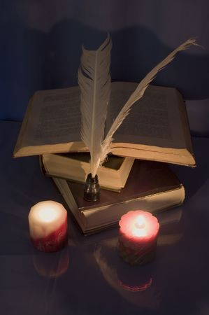Ancient books light of candle with retro objects photo