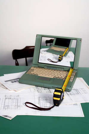 metre: Architecture planning with metre and laptop on desk - focus on first plane