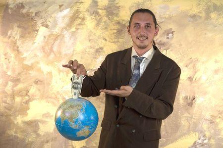 Businessman holding globe with money - Parody on earning money photo