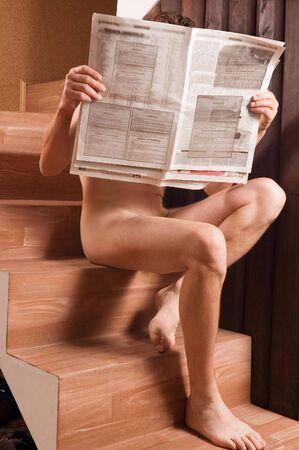 uomini nudi: Nudo maschile seduto su sedie con giornali  Archivio Fotografico