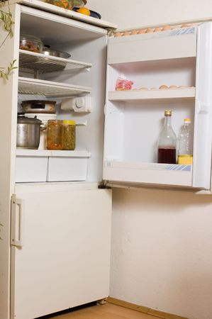 Open refrigerator in kitchen full of the food