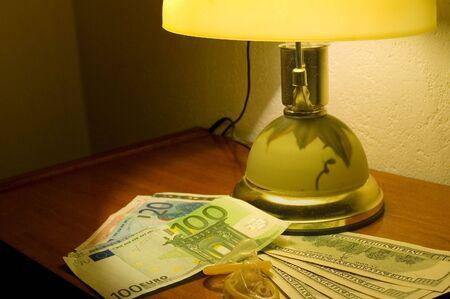 educacion sexual: Preservativos y dinero al lado de la l�mpara de la habitaci�n de hotel