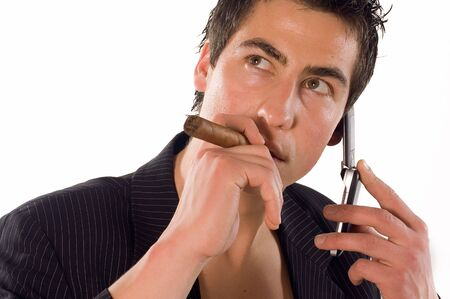 young adult man: Young adult man using his mobile phone and smoking cigarette Stock Photo