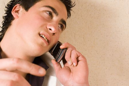 young adult man: Young adult man using his mobile phone Stock Photo