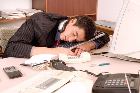 Businessman sleeping in his office at table with computer Stock Photo