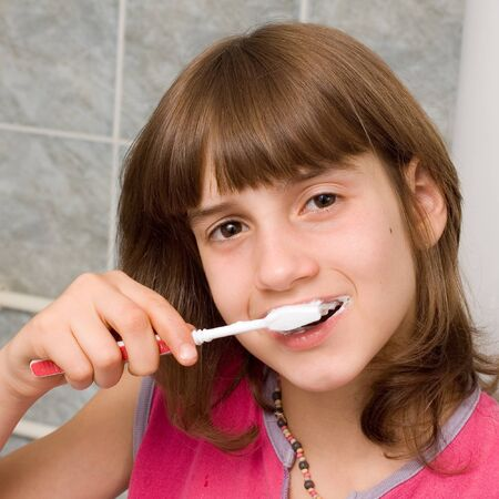 Young child brushing her teeth in bathroom Stock Photo - 1439647