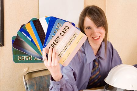 creditcards: Young woman holding credit cards. helmet on table