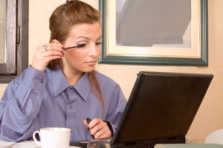 Business woman at office applying make up, at frame on wall is laptop from desk photo