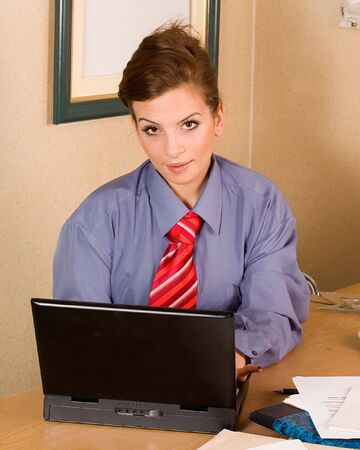 Young business woman at office working with laptop photo