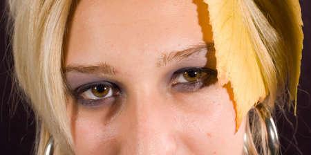 close up eye: Vicino agli occhi della giovane donna con foglie cadere sulla faccia