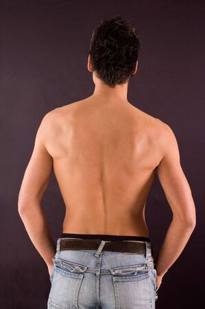 Male torso from back view on dark backgrounds